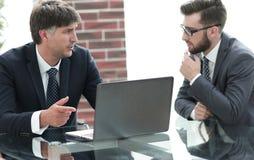 Deux hommes d'affaires travaillant sur un ordinateur portable dans le bureau Images libres de droits