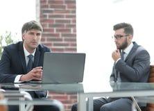 Deux hommes d'affaires travaillant sur un ordinateur portable dans le bureau Photographie stock libre de droits