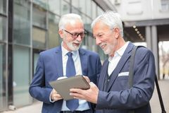 Deux hommes d'affaires d'une chevelure gris supérieurs de sourire heureux travaillant à un comprimé photo stock