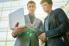 Deux hommes d'affaires utilisant l'ordinateur portable dehors Photo stock