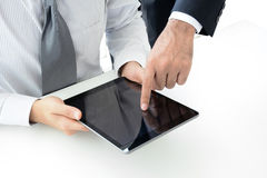 Deux hommes d'affaires utilisant la tablette avec un écran tactile de main Photographie stock libre de droits