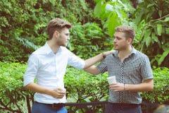 Deux hommes d'amis parlant la position dans un jardin Photographie stock libre de droits