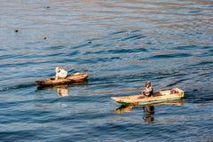 Deux hommes dans des canoës de pirogue sur le lac Atitlan, Guatemala photographie stock