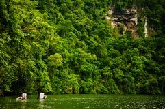 Deux hommes dans des canoës sur le fleuve doux photo stock