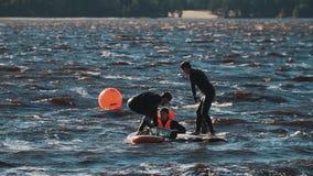 Deux hommes dans des gilets de vie combattant avec les panneaux surfants de battes molles dans l'eau clips vidéos