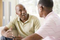 Deux hommes dans la salle de séjour parlant et souriant Photographie stock
