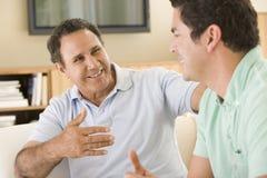 Deux hommes dans la salle de séjour parlant et souriant Photographie stock libre de droits