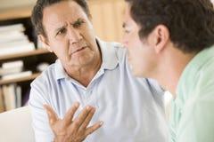 Deux hommes dans parler de salle de séjour Image libre de droits