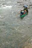Deux hommes dans un canoë dirigeant la rapide sauvage de rivière Images stock