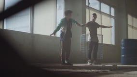Deux hommes dansant dans la salle sombre et poussi?reuse du b?timent abandonn? Adolescents entreprenant la d?marche de danse simu banque de vidéos