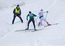 Deux hommes de ski de pays croisé sprintant vers le haut, un tombe Images stock