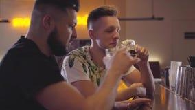 Deux hommes de sourire adultes s'asseyant au compteur de barre souriant et parlant Homme barbu partageant avec émotion son problè banque de vidéos