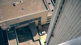 Deux hommes de sportifs descendent vers le bas du haut mur de maison de gratte-ciel clips vidéos