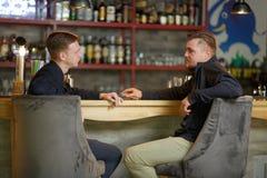 Deux hommes des amis, s'asseyent dans une barre à la barre et causent au sujet de quelque chose intéressante Photographie stock