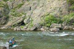Deux hommes dirigent une rivière rocheuse en Alaska à distance Photo libre de droits