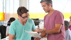 Deux hommes discutant le document dans le bureau créatif clips vidéos