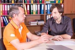 Deux hommes discutent dans le bureau Photos libres de droits