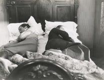 Deux hommes dormant avec leurs dos entre eux Photos stock