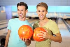 Deux hommes effectuent la ligne à partir des billes dans le club de bowling Images stock