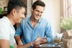 Deux hommes employant l'Internet de tablette, mélange asiatique Photos stock