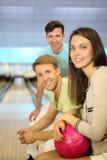 Deux hommes et femme avec la bille s'asseyent dans le club de bowling Images stock