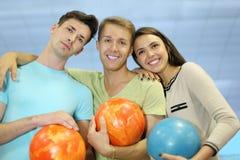 Deux hommes et femme retiennent des billes dans le club de bowling Image stock