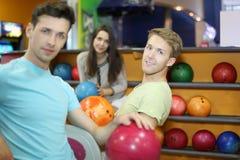 Deux hommes et femme s'asseyent dans le club de bowling Image stock