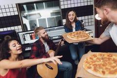 Deux hommes et deux femmes dans le studio d'enregistrement mangent de la pizza photo libre de droits