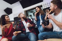 Deux hommes et deux femmes dans le studio d'enregistrement mangent de la pizza image stock