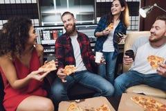 Deux hommes et deux femmes dans le studio d'enregistrement mangent de la pizza images libres de droits