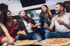 Deux hommes et deux femmes dans le studio d'enregistrement mangent de la pizza image libre de droits