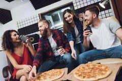 Deux hommes et deux femmes dans le studio d'enregistrement mangent de la pizza photos libres de droits