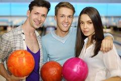 Deux hommes et fille retiennent des billes dans le club de bowling Photographie stock