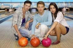 Deux hommes et fille s'asseyent avec des billes dans le club de bowling Photo libre de droits