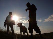 Deux hommes et un chien dans le coucher du soleil Photos stock