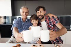 Deux hommes et un garçon posent dans la cuisine avec les tasses de thé qui sont jugées sur des bras tendues Images stock