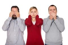 Deux hommes et une femme montre trois singes sages Photographie stock