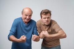 Deux hommes forts mûrs, soulevant les poings serrés montrant leur puissance photo libre de droits