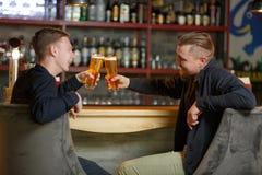 Deux hommes gais des amis, s'asseyent dans une barre, boivent d'une bière froide régénératrice et font tinter des verres Photo stock
