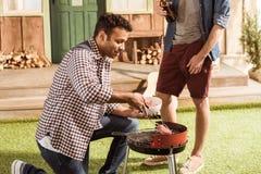 Deux hommes grillant des hamburgers tout en buvant de la bière ensemble Image libre de droits