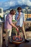 Deux hommes grillant tout entier Image stock