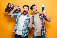 Deux hommes heureux dans des chemises se tenant avec la valise et le passeport Images stock