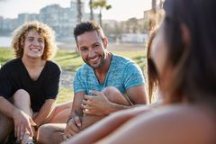 Deux hommes heureux s'asseyant avec des amis en dehors de rire Photos stock