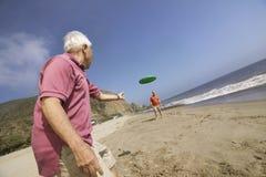 Deux hommes jouant avec le disque de vol sur la plage Image stock