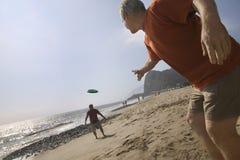 Deux hommes jouant avec le disque de vol sur la plage Photographie stock libre de droits