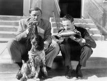 Deux hommes jouant deux harmonicas avec un poseur anglais (toutes les personnes représentées ne sont pas plus long vivantes et au Photo libre de droits