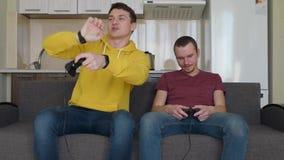 Deux hommes jouent le jeu vidéo et la victoire banque de vidéos