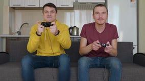 Deux hommes jouent le jeu vid?o et la victoire banque de vidéos