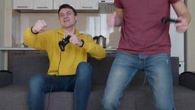 Deux hommes jouent le jeu vid?o et la victoire clips vidéos