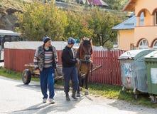 Deux hommes mènent par le frein d'un cheval armé à un chariot dans une banlieue de ville de son en Roumanie Photos libres de droits